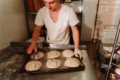 Хлебопек делает ручные взрезы на тесте для хлеба Изготовление хлеба bakersfield стоковое изображение