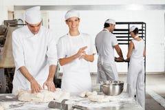 Хлебопек делая шарики теста мужским коллегой в хлебопекарне Стоковые Изображения