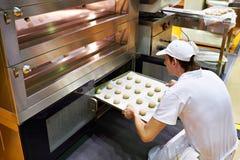 Хлебопек кладет поднос шариков теста для того чтобы испечь плюшки в печь Стоковые Изображения RF