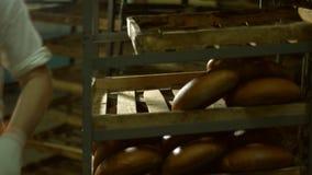 Хлебопек кладет свеже испеченный хлеб на полки сток-видео
