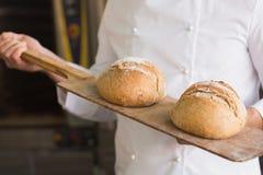 Хлебопек показывая поднос свежего хлеба Стоковые Изображения RF