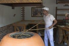 Хлебопек принимает вне готовый хлеб пита от tandoor стоковое изображение