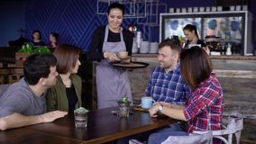 Хлебосольная молодая официантка на кафе принося напитки в покрашенных кружках к клиентам 4 друз сидя на акции видеоматериалы