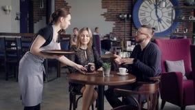Хлебосольная молодая официантка принося напиток в коричневой керамической кружке к таблице для женщины Пары сидя на акции видеоматериалы