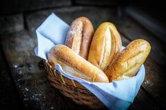 Хлебцы в корзине на деревенской деревянной предпосылке Стоковое фото RF