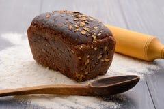 Хлеб, вращающая ось и деревянные ложки на таблице Стоковое фото RF