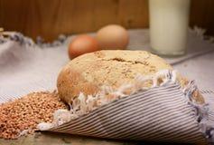 Хлеб гречихи, стекло молока и яичка на деревянном столе жизнь страны все еще Стоковое Фото