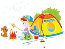 Хлеб жарки разведчика мальчика на лагерном костере Стоковая Фотография