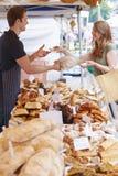 Хлеб женщины покупая от стойла рынка Стоковые Изображения
