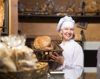 Хлеб зрелого работника хлебопекарни предлагая Стоковая Фотография RF