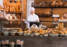 Хлеб зрелого работника хлебопекарни предлагая Стоковые Изображения RF