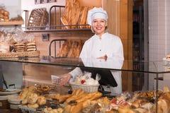 Хлеб зрелого работника хлебопекарни предлагая Стоковое Фото