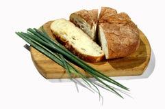 Хлеб и зеленый лук на изолированной разделочной доске Стоковое фото RF