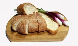Хлеб и зеленый лук на разделочной доске на белой изолированной предпосылке, Стоковые Изображения