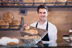Хлеб и печенье работника хлебопекарни человека предлагая Стоковая Фотография RF