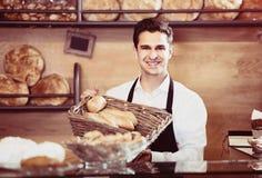 Хлеб и печенье работника хлебопекарни человека предлагая Стоковое Изображение