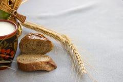 Хлеб и пшеница с чашкой молока на серой ткани Стоковая Фотография RF