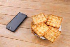 Хлеб и телефон положили дальше таблицу стоковые фото