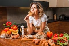 Хлеб довольно молодой домохозяйки сдерживая в ее руках стоковое изображение