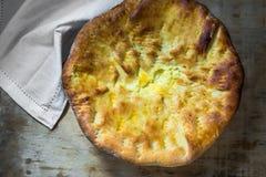 Хлеб очень вкусного домодельного сыра плоский с золотой коркой на постаретой деревянной таблице, белом взгляд сверху салфетки Стоковые Фотографии RF