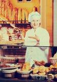 Хлеб работника хлебопекарни предлагая Стоковые Изображения RF