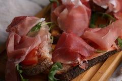 Хлеб с беконом, arugula и томатом на деревянные доски Селективный фокус Стоковые Фото
