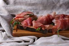 Хлеб с беконом, arugula и томатом на деревянные доски Селективный фокус Стоковая Фотография RF