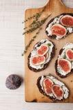 Хлеб с свежим сыром, смоквой и sprig на тимиане на вертикали деревянной доски Стоковое Изображение