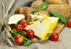 Хлеб, томаты вишни, сыр и базилик на деревянной разделочной доске Стоковое фото RF