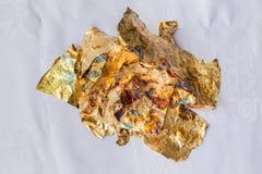 Царапины сусального золота, рассеиванные дальше на бумажной предпосылке стоковая фотография rf