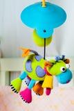 Цветастая поворачивая игрушка младенца коровы над кроватью Стоковая Фотография RF