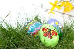 Цветастая рука покрасила пасхальные яйца в зеленой траве Стоковое фото RF
