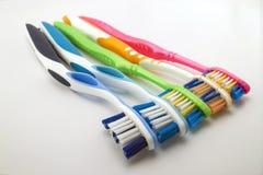 Цветастые зубные щетки на белой предпосылке с космосом экземпляра Макрос стоковые изображения rf