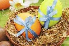 Цветастые пасхальные яйца в корзине Стоковые Изображения