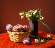 Цветастые пасхальные яйца в корзине и snowdrops Стоковое Фото