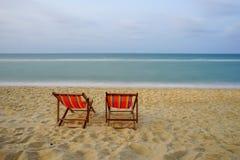 Цветастые стулы на пляже стоковая фотография