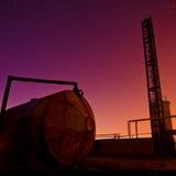 Цветастый заход солнца за промышленными краном и танком Стоковое Фото