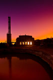 Цветастый заход солнца за промышленным зданием Стоковые Изображения RF