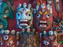 Цвета тварей ритуальной тибетской волшебной маски религиозные буддийские, красных и белых на красной предпосылке Стоковые Изображения RF