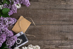 Цветение сирени на деревенской деревянной предпосылке с пустым космосом для приветствуя сообщения Камера, малый конверт Взгляд св Стоковое фото RF
