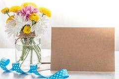 Цветет букет в вазе опарника с примечанием карточки, конвертом и голубой лентой на белой деревянной деревенской предпосылке Стоковые Изображения