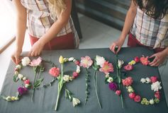Цветет взгляд сверху поставки Слово ВЕСНА creatin флористов сделанная из цветков на предпосылке против детенышей весны цветка при Стоковые Изображения