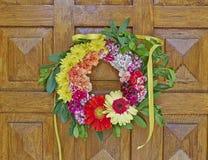 Цветет смертная казнь через повешение венка на деревянной двери Стоковое фото RF