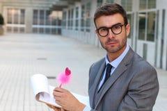 Цветистый бизнесмен принимая примечания с милой розовой ручкой стоковые фото
