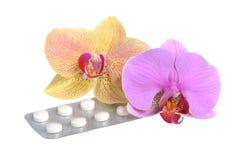 2 цветка орхидеи при фильм-покрытые изолированные таблетки Стоковое Фото