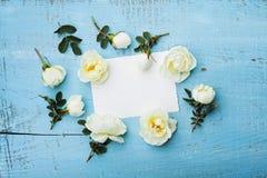 Цветки белой розы, листья зеленого цвета и чистый бумажный лист на взгляд сверху предпосылки бирюзы винтажном в стиле положения к Стоковое Изображение