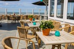 Цветки в баке и свечах на таблицах кафа пляжа стоковые фото