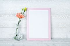 Цветки в вазе и рамке фото на деревянной предпосылке Стоковые Фотографии RF