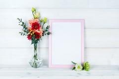 Цветки в вазе и рамке фото на деревянной предпосылке Стоковые Фото