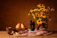 Цветки в вазе, книгах и грушах стоковое фото